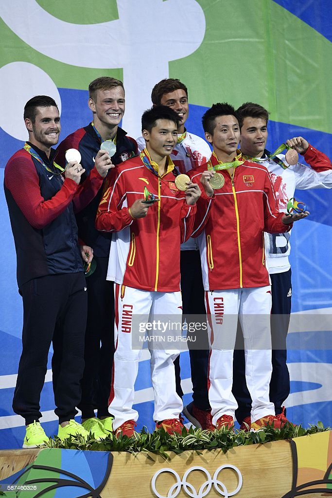 Great Britain's Thomas Daley and Great Britain's Daniel Goodfellow (white jersey, bronze), China's Chen Aisen and China's Lin Yue (red jersey, gold) and US David Boudia and US Steele Johnson (dark jersey, silver) celebrate during the podium ceremony for the Men's Synchronised 10m Platform contest during the diving event at the Rio 2016 Olympic Games at the Maria Lenk Aquatics Centre in Rio de Janeiro on August 8, 2016. / AFP / Martin BUREAU