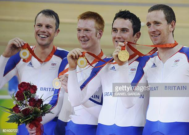 Great Britain's track cyclists Paul Manning Ed Clancy Geraint Thomas and Bradley Wiggins pose for photographers after winning the gold medal in the...