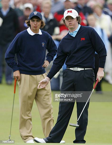 Great Britian and Ireland golfer Rory McIlroy follows his putt 09 September 2007 on the 14th green as Rickie Fowler of the USA looks on during the...