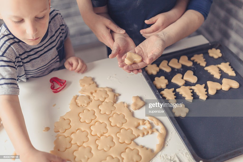 Two brothers and a mother are having a good time while making cookies. They play with a dough and flour. The kids are wearing T-shirts and mother is wearing blue blouse. They make cookies by cutting dough to flower and heart shapes.