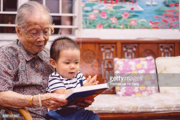 great grand mother reading story book to her great grandson joyfully