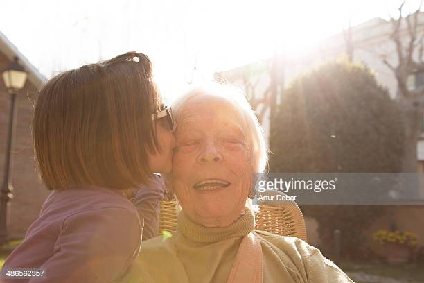 great granddaughter kissing his great grandmother. - great granddaughter stock photos and pictures