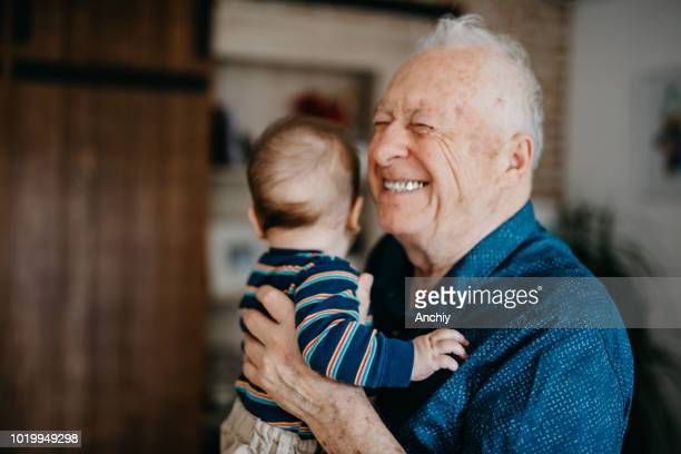 great grandfather filled with joy embracing his great grandson - grandfather stock pictures, royalty-free photos & images