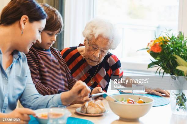 Great grandmother and mother looking at boy using smart phone in house