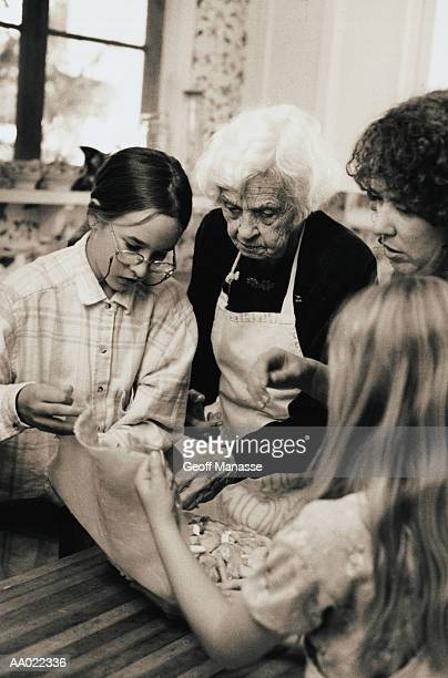 great grandmother and mother teach girls to bake - great granddaughter stock photos and pictures