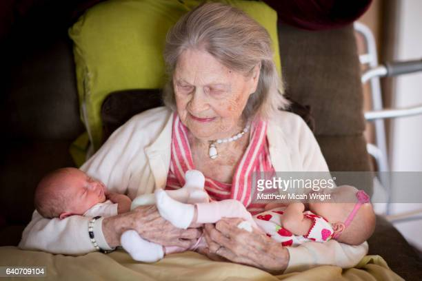 A great grandmother holding a pair of newborn twin great grandkids.