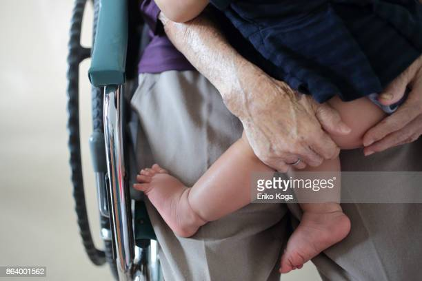 great grandmother holding her great granddaughter on wheelchair - great grandmother stock pictures, royalty-free photos & images