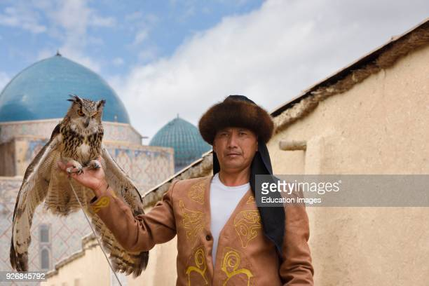 Great Horned Owl and handler with domes of Khoja Ahmed Yasawi mausoleum Turkestan Kazakhstan.