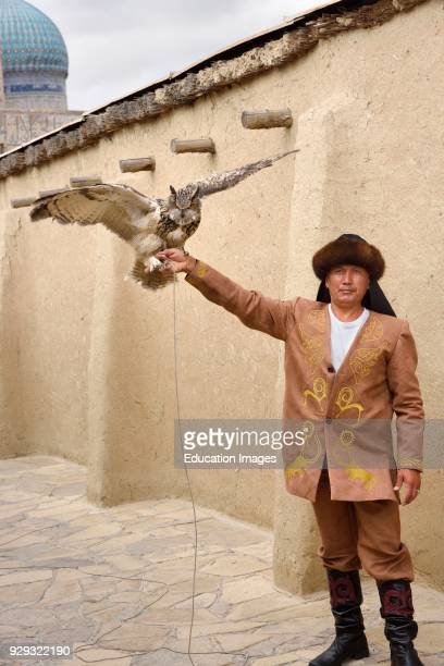 Great Horned Owl and handler with ribbed dome of Khoja Ahmed Yasawi mausoleum Turkestan Kazakhstan
