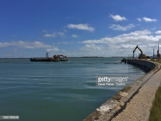 great salterns quay being demolished by heavy machinery from a floating barge. - portsmouth england stock pictures, royalty-free photos & images