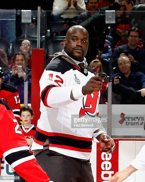NBA great Shaquille O'Neal holds up the hockey puck after participating in the ceremonial puck drop before an NHL hockey game between the Florida...
