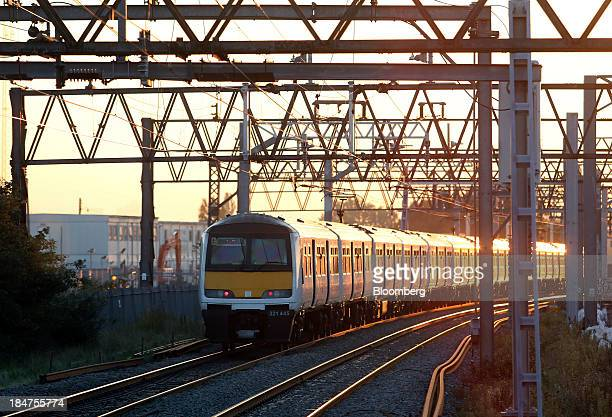 A Greater Anglia rail passenger train operated by Abellio Transport Holding BV passes beneath electrical wiring as it approaches a platform at...
