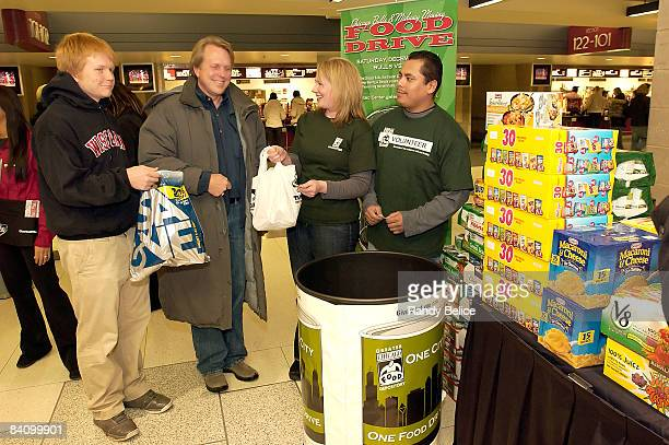 Greater Chicago Food Depository Director of External Affairs Leah Ray and volunteer Juan Villanueva receive non perishable food items from Greg...