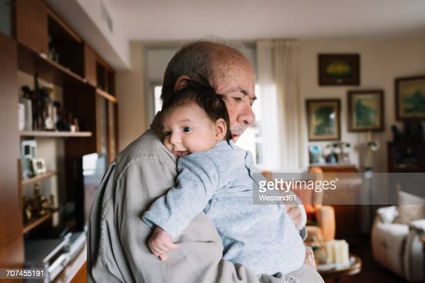 great-grandfather holding baby at home - zuid europese etniciteit stockfoto's en -beelden