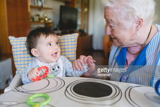 Great-grandmother playing with a baby girl sitting in the high chair next to the table with toys