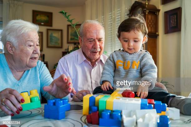 great-grandparents and baby girl playing together with plastic building bricks at home - the_writer's_block stock pictures, royalty-free photos & images