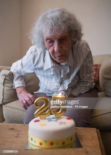 Greatgreat grandmother Doris Cleife blows out candles showing the number 25 on a birthday cake in her flat at Housing 21's Brunel Court in Portsmouth...