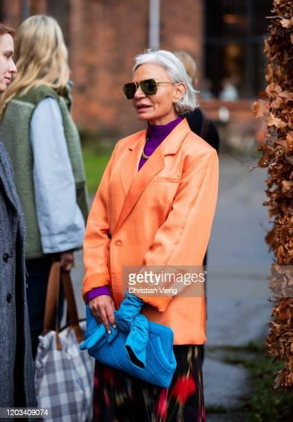 Grece Ghanem is seen wearing orange blazer, purple turtleneck, blue clutch, gloves outside Baum und Pferdgarten during Copenhagen Fashion Week...