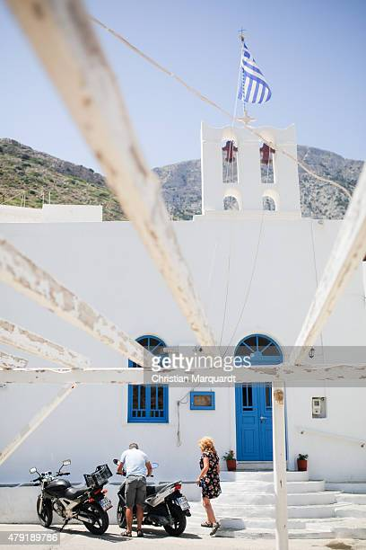 Greec national flag flies above a old Greec orthodox church beyound local residens prepare to ride a motobike during midday in the town of Kameras on...