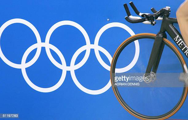 A cyclist warms up beside the Olympic rings before the men's individual pursuit qualifying against Australian Bradley McGee at the Athens velodrome...