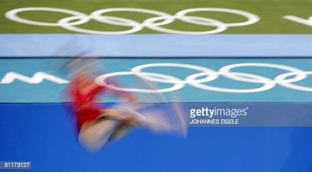 A gymnast performs on the floor during the women's Artistic Gymnastics qualifications 15 August 2004 at the Olympic Indoor Hall during the Athens...