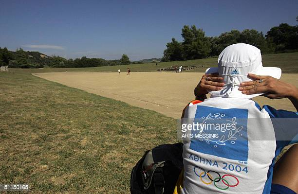 A volunteer of Athens 2004 Olympic Games sits in the ancient stadium of Olympia where the Olympic Games were born in 776 BC 07 August 2004 Ancient...