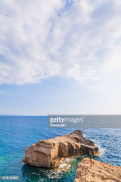 Greece, Aegean Islands, Rhodes, young man looking to rocky island