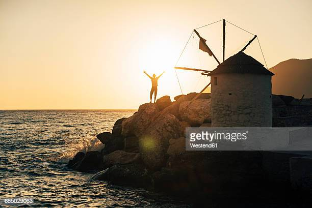 greece, amorgos, aegialis, silhouette of man with arms raised near wind mill at sunset - cyclades islands stock pictures, royalty-free photos & images