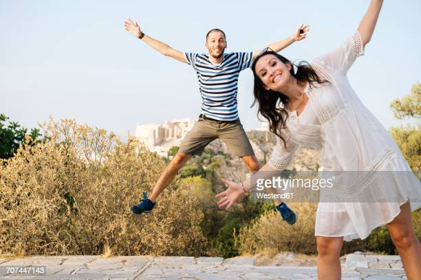 Greece, Athens, happy couple jumping at Areopagus with The Acropolis and Parthenon in the background