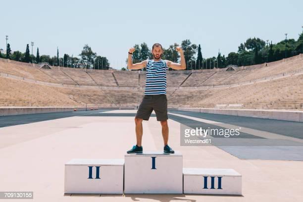 greece, athens, man on the podium celebrating in the panathenaic stadium - winners podium stockfoto's en -beelden