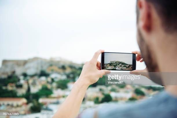 Greece, Athens, man taking a cell phone picture of the Parthenon temple in the Acropolis surrounded by the city