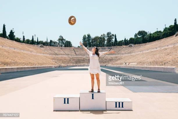 greece, athens, woman on the podium celebrating in the panathenaic stadium - winners podium stock-fotos und bilder