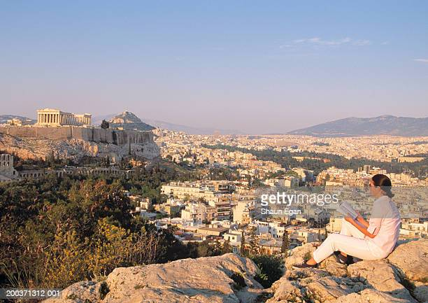 Greece, Athens, woman reading by view of Acropolis and cityscape