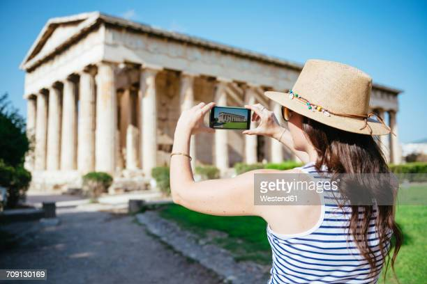 greece, athens, woman taking a cell phone pictire of the hephaisteion in the agora - temple grec photos et images de collection