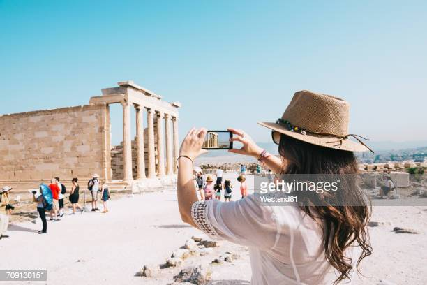 greece, athens, woman taking a cell phone picture of the erechtheion temple in the acropolis - grécia - fotografias e filmes do acervo