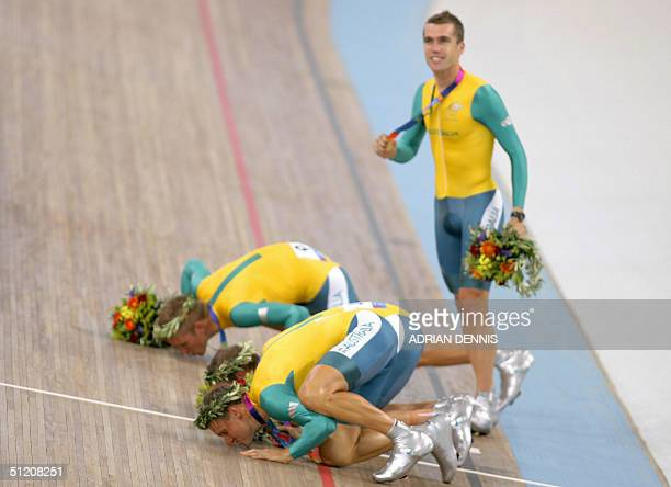 Australian riders kiss the track ad their teammate Bradley McGee stares away at the end of the men's team pursuit finals at the Athens velodrome...