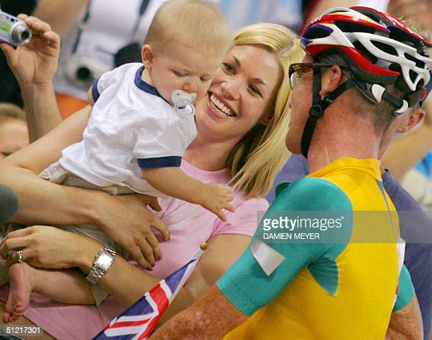 Australia's Stuart O'Grady celebrates with his wife AnneMarie holding their son Seth following his gold medal victory with partner Graeme Brown in...