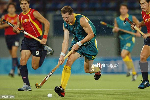 Australia's Travis Brooks breaks away from Spain's Pol Pablo Amat in their semifinal match of the men's hockey competition at the 2004 Olympic Games...