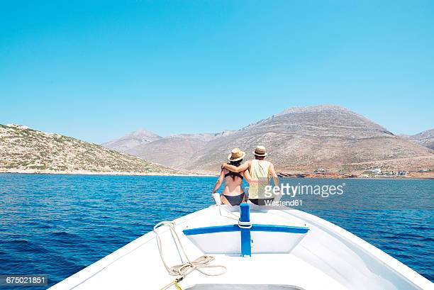 Greece, back view of couple sitting arm in arm on bow of a boat looking at Amorgos Island