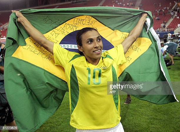 Brazilian forward Marta carries her national flag at the end of the gold medal football match against USA at the Olympic Games 26 August 2004 at...