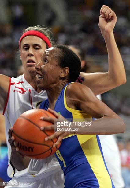 Brazil's captain Janeth Arcain dribbles past Spain's Madariaga Valdemoro in the women's basketball quarterfinals match against Spain 25 August 2004...