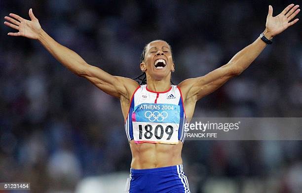 Britain's Kelly Holmes celerbates as she crosses the finish line first for the gold in the women's 1500m final 28 August 2004 during the Olympic...