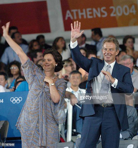 British Prime Minister Tony Blair and his wife Cherie wave as they attend the opening ceremony of the summer Olympic Games in Athens 13 August 2004....