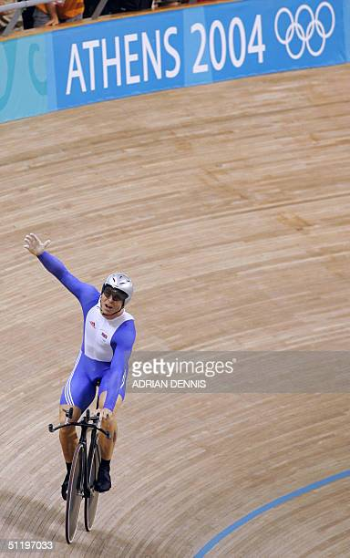 Briton Chris Hoy celebrates after wining the men's 1 km time trial final at the Athens velodrome during the cycling track competition at the 2004...