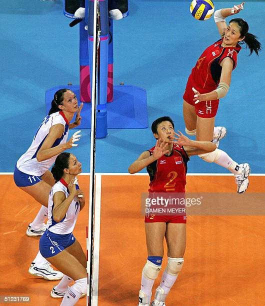 Chinese captain Feng Kun sets the ball to her teammate Yang Hao as their Russian opponents Russian Ekaterina Gamova and Irina Tebenikhina get ready...