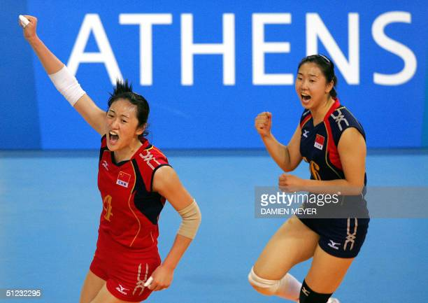 Chinese Liu Yanan and her teammate Zhang Na celebrate their team's victory over Russia at the end of their gold medal volleyball match at the Olympic...