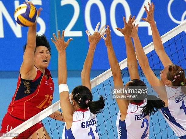 Chinese Wang Lina smashes despite her Russian opponents Ekaterina Gamova Irina Tebenikhina and Russian Marina Sheshenina during the gold medal...