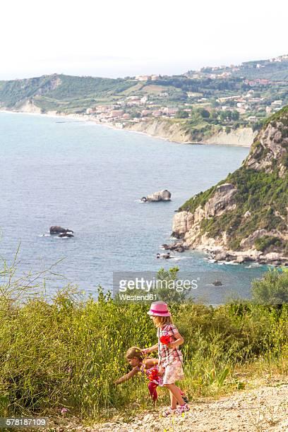 Greece, Corfu, Afionas, two little girls picking flowers