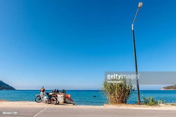 greece, corfu, agios georgios, moped and street lamp at the ocean - straßenrand stock-fotos und bilder