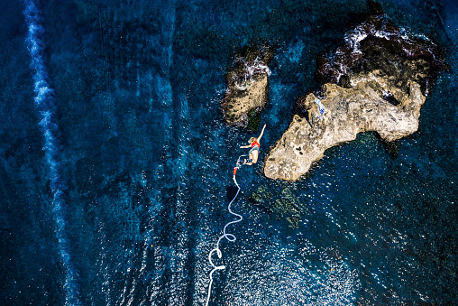 Greece, Crete, Bungee Jumping, woman jumping bungee over sea - gettyimageskorea